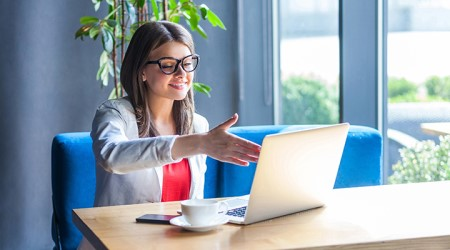 Young woman extending a handshake to her laptop screen